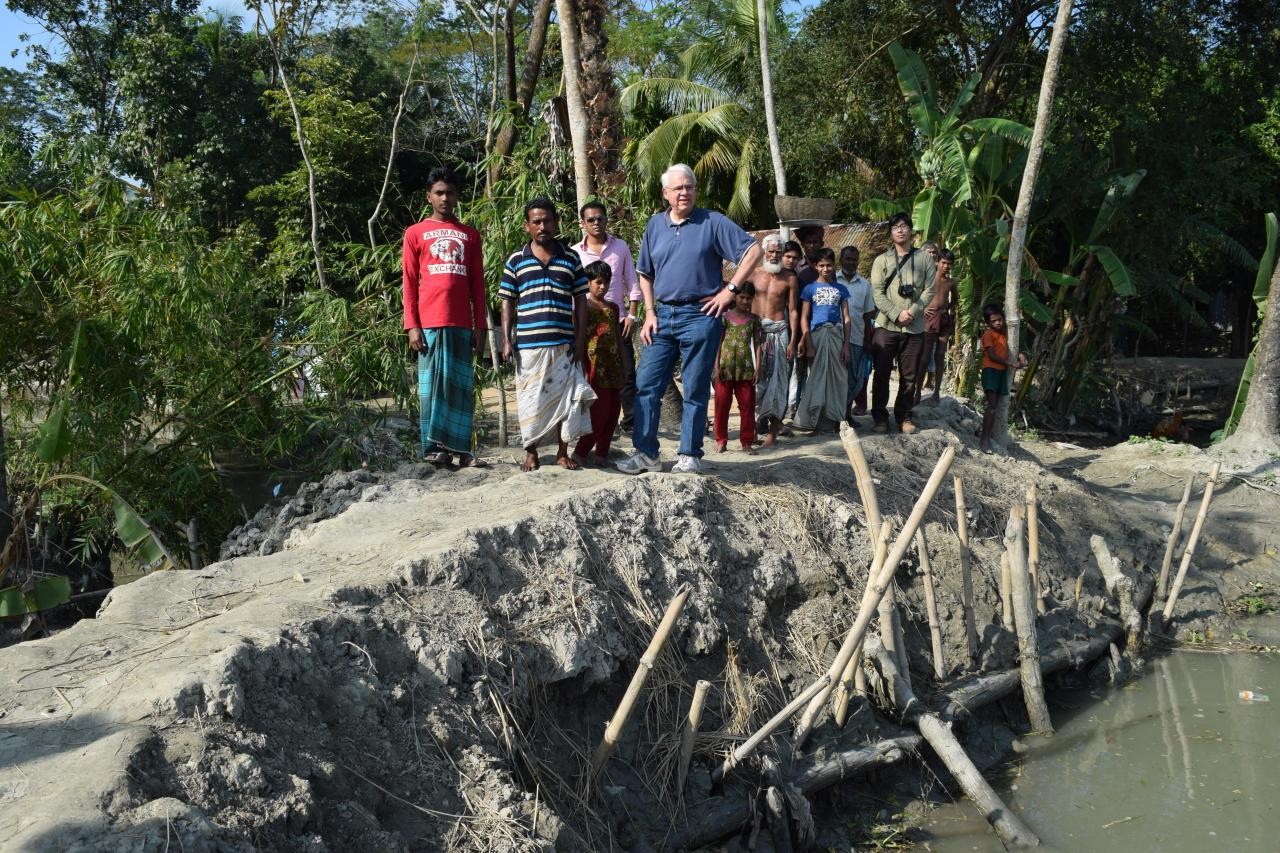Ohio State researcher J. Craig Jenkins stands with local residents in Bangladesh on the remains of an eroding embankment.