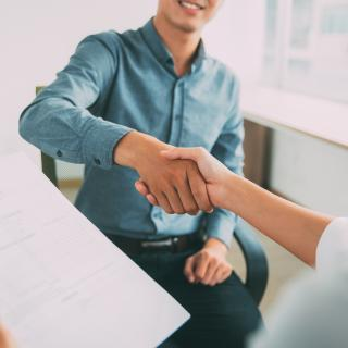 Man shaking hands with employer.
