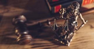 Close-Up Of Lady Justice On Wooden Table