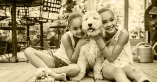 Image of girls hugging a dog
