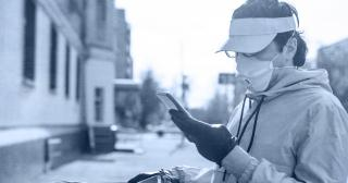 Image of man in mask looking at phone